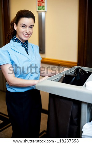 Female attendant posing with cart in hotel corridor - stock photo