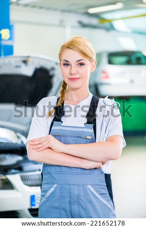 Female auto mechanic working in car workshop - stock photo