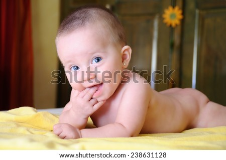Female Baby bites the hand on a yellow towel on the bed - stock photo