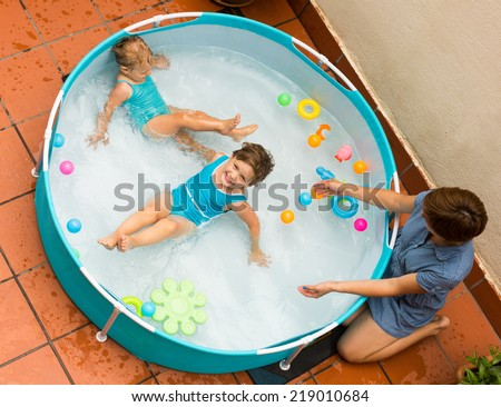 Female baby-sitter with two little girls at inflatable pool - stock photo