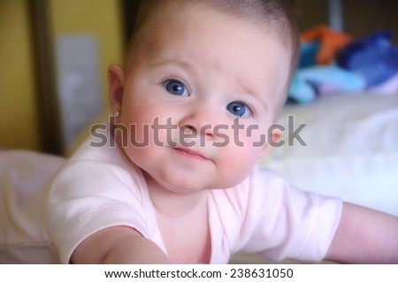 Female baby with pink body on the bed with direct gaze - stock photo