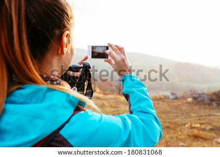 Female backpacker taking a photo of a landscape - stock photo