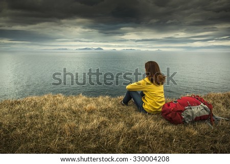 Female backpacker tourist in Icleand resting after a long day of adventures - stock photo