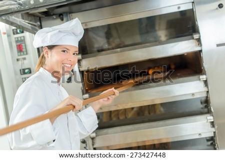 Female baker at bread oven - stock photo