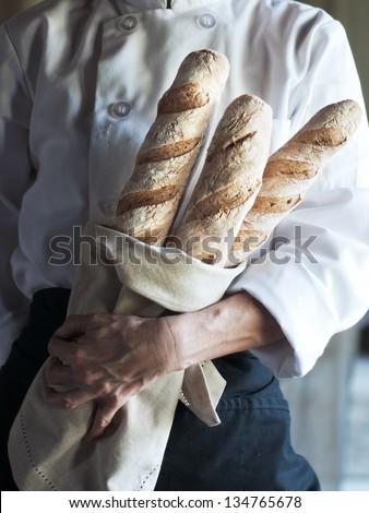 Female baker holding fresh baked French baguette - stock photo
