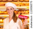 """Female baker or saleswoman in her bakery selling fresh bread, pastries and bakery products, she hold a sign in her hand saying """"offer"""" in German - stock photo"""