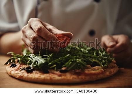 Female baker preparing pizza with ham, arugula and cherry tomatoes. Mediterranean cuisine. - stock photo