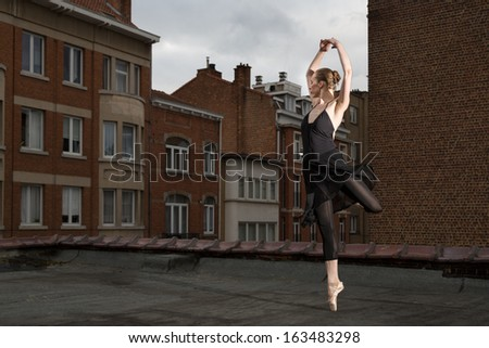 Female ballet dancer in black dress performs pointe rotation with her arms closed above the head on a rooftop in a city - stock photo