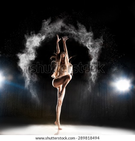 female ballet dancer posing on stage in theater with powder - stock photo