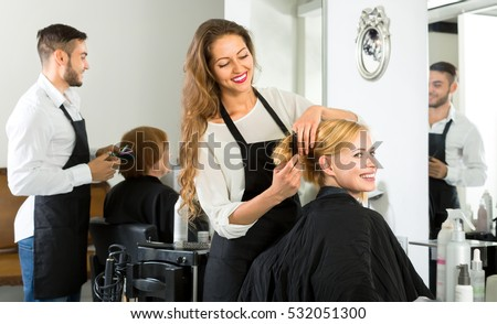 Female barber combing woman's hair at a hair salon
