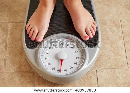 Female bare feet on weight scale, top view