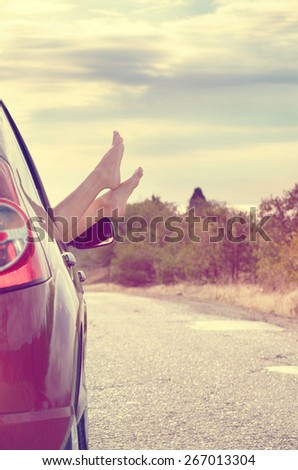 Female bare feet stick out of car window on mountain background. Travel concept. - stock photo