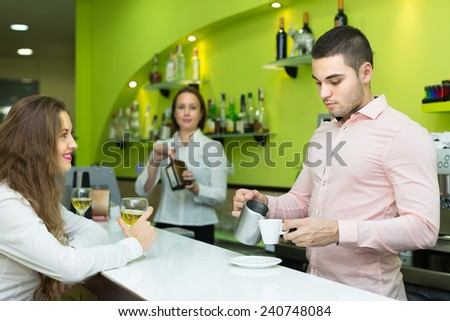 Female bartender and handsome young male barista working at bar. Focus on man  - stock photo