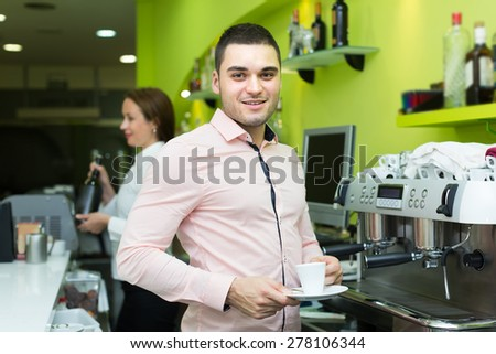 Female bartender and young handsome male barista working at bar. Focus on man