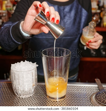 Female bartender is adding an ingredient to the glass - stock photo