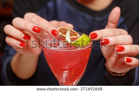 Female bartender is adding citrus zest to cocktail - stock photo