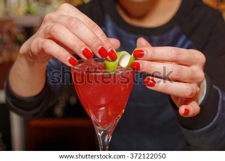 Female bartender is adding lime zest to cocktail - stock photo