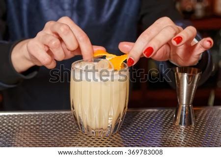 Female bartender is adding orange zest to cocktail - stock photo