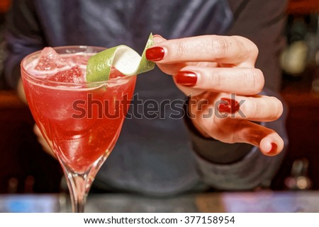 Female bartender is decorating a cocktail with lime zest, toned - stock photo