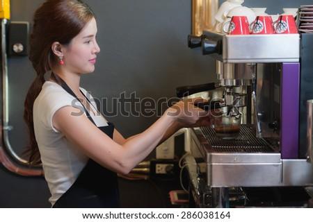 Female bartender makes coffee using coffee machine. - stock photo