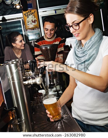 Female bartender pours the beer into a glass - stock photo