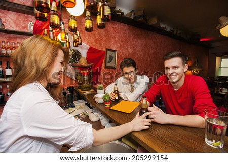 Female bartender serving beer to men at bar counter - stock photo