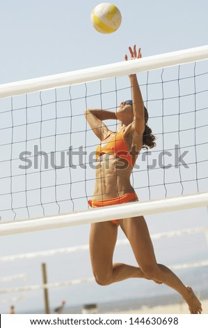Female beach volleyball player jumping to spike volleyball over net - stock photo