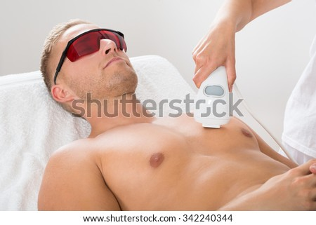 Female Beautician Giving Laser Epilation On Man's Chest - stock photo