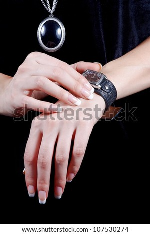 Female beautiful hands with manicure touch a watch for time definition - stock photo