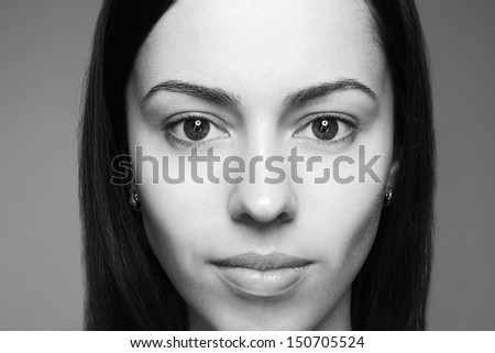 Female beauty concept. Portrait of a smiling beautiful brunette girl with alien-like face posing over gray background. Healthy hair & skin. Close up. Black & white (monochrome) studio shot