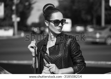 Female beauty concept. Portrait of fashionable young girl in casual black jeans, black jacket, white crop-top, sunglasses and small  bag posing on the street. Perfect hair. Vogue style. outdoor shot - stock photo