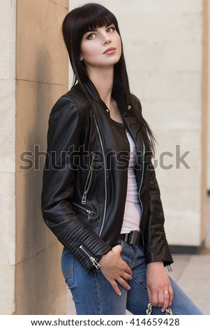 Female beauty concept. Portrait of fashionable young girl in casual black jeans, black jacket, white crop-top and small ba g posing on the street. Perfect hair & skin. Vogue style. outdoor shot - stock photo
