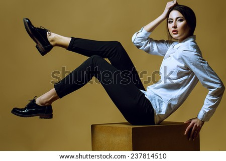 Female beauty concept. Portrait of fashionable young girl in classic clothes posing over gold background. Perfect hair & skin. Vogue style. Studio shot - stock photo