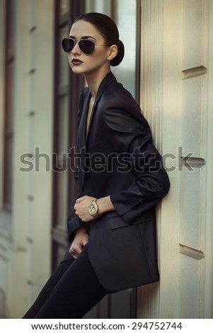 Female beauty concept. Portrait of fashionable young girl in classic clothes (suit) and sunglasses posing on the street. Perfect hair & skin.  outdoor shot - stock photo