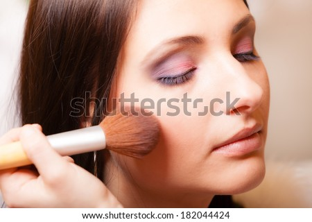Female beauty. Makeup artist applying with brush powder or rouge on check of her client young woman. Girl by visagiste.