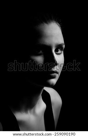 female beauty portrait on black background low key monochrome image - stock photo