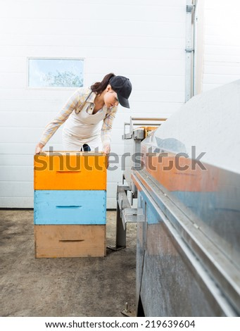 Female beekeeper with stacked honeycomb crates working in beekeeping factory - stock photo