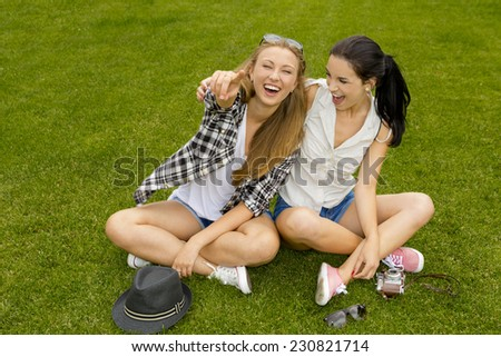 Female best friends sitting on the grass and having a good time - stock photo