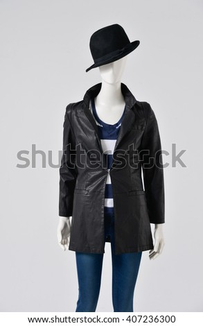 female black clothes with hat on a mannequin-gray background - stock photo