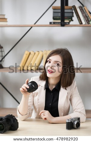 Female blogger tells interesting fact about photo. Attractive young woman with camera lens in hand talking about photographing. Did you know concept