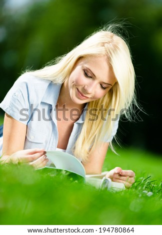 Female blonde student reads the book lying on the green grass in the park