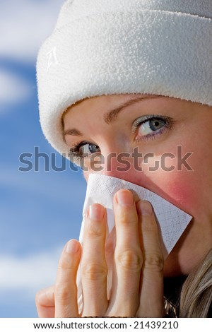 Female blowing her nose (blue sky background)