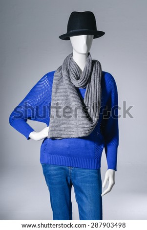 female blue clothing in jeans with scarf, black hat on mannequin on light background - stock photo