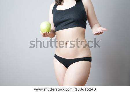 Female body with green apple on gray background. Weight loss, diet - stock photo