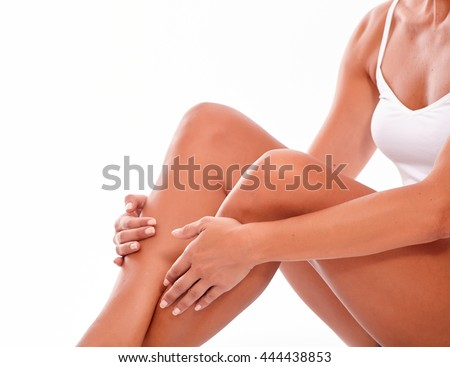 Female body with knees bent sitting down and holding hands on calves while wearing a white tank top on a white background