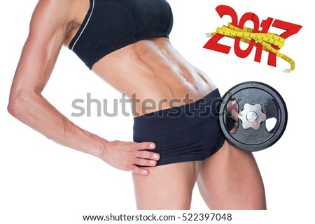 Female bodybuilder holding large black dumbbell mid section against digitally generated image of 3D new year with tape measure