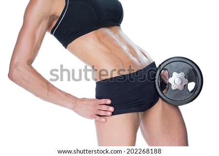 Female bodybuilder holding large black dumbbell mid section on white background - stock photo