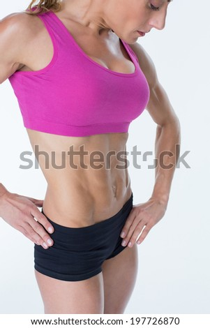 Female bodybuilder posing in pink sports bra on white background