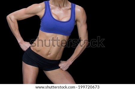 Female bodybuilder posing with hands on hips mid section on black background