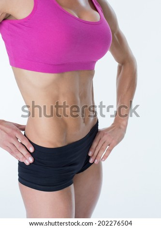 Female bodybuilder posing with hands on hips mid section on white background